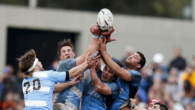 Scaglione and Panceyra of Argentine national rugby team compete for the ball with de Freitas, Lamanna and Echeverria of Uruguay's national rugby team during a friendly match in Montevideo
