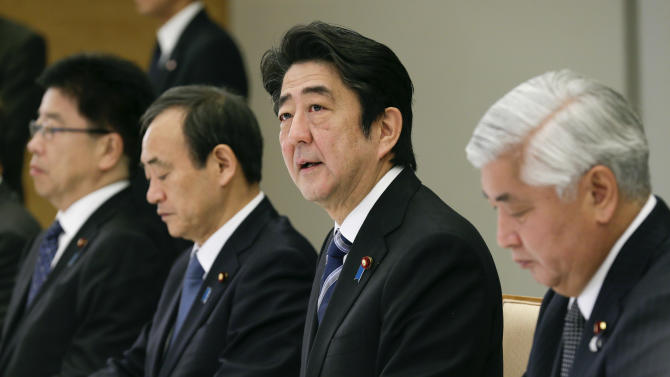 Japanese Prime Minister Shinzo Abe (C) talks during a ministerial meeting on an online video purportedly showing a Japanese hostage being killed by the Islamic State group, in Tokyo on February 1, 2015