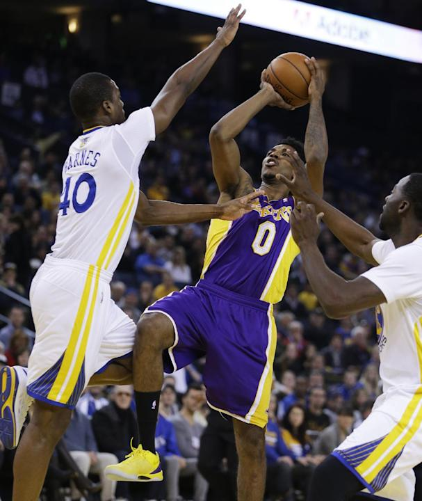 Los Angeles Lakers' Nick Young (0) shoots between Golden State Warriors' Harrison Barnes, left, and Draymond Green during the first half of an NBA basketball game Saturday, Dec. 21, 2013, in O
