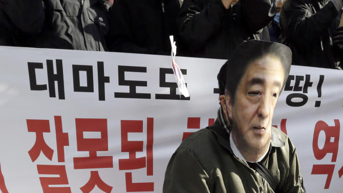 FILE - In this Friday, March 1, 2013 file photo, a South Korean protester playing the role of Japan's Prime Minister Shinzo Abe kneels down on a Japanese flag during a rally demanding full compensation and apology for wartime sex slaves from Japanese government and criticizing the Japanese government's recent claim over the disputed islets called Dokdo in South Korea and Takeshima in Japan, in front of the Japanese Embassy in Seoul, South Korea. Japan has acknowledged that it conducted only a limited investigation before claiming there was no official evidence that its imperial troops coerced Asian women into sexual slavery before and during World War II. A parliamentary statement signed Tuesday, May 7 by Abe acknowledged a document produced by a postwar international military tribunal containing a Japanese soldier's testimony about abducting Chinese women as military sex slaves. (AP Photo/Lee Jin-man, File)