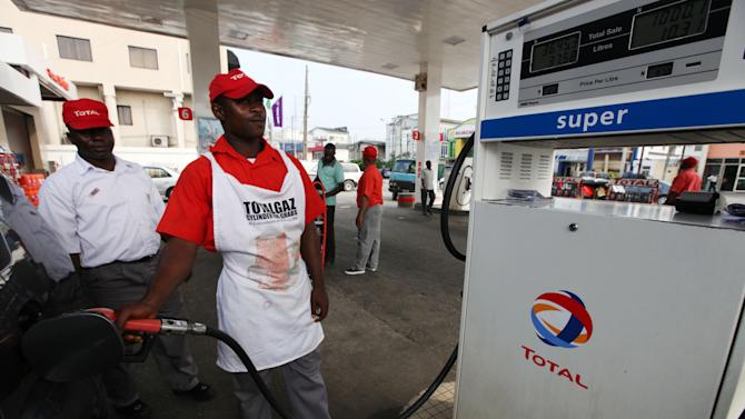 A petrol attendant fills a car at a Total petrol station in Lagos, Nigeria, Monday, Nov. 19, 2012. French oil company Total SA said Monday it had sold its stake in an offshore oil field near Nigeria for $2.5 billion to the Chinese state-run firm Sinopec Corp., a sign of the China's growing stakes in the West African nation's oil production. (AP Photo/Sunday Alamba)