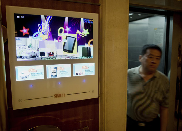 A Chinese man walks past a TV advertising screen by Focus Media Holding Ltd. on display near an apartment lift in Beijing Tuesday, Aug. 14, 2012. Just a few years after Chinese companies lined up to sell shares on Wall Street, a growing number are reversing course and pulling out of U.S. exchanges. This week, Focus Media Holding Ltd., announced its chairman and private equity firms want to buy back its U.S.-traded shares and take the Shanghai-based advertising company private. The deal would value Focus Media at $3.5 billion, according to financial information firm Dealogic. (AP Photo/Andy Wong)