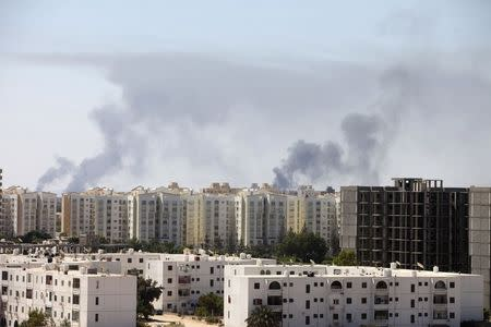 Smoke rises above buildings after heavy fighting between rival militias broke out near the airport in Tripoli