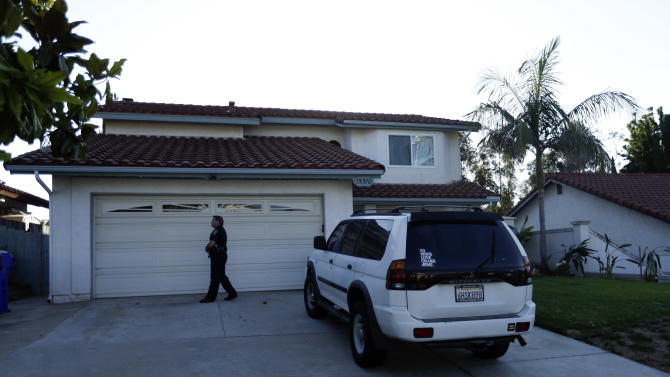 A San Diego police officer stands in front of the home of the mother of Colorado shooting suspect James Holmes Friday, July 20, 2012, in San Diego. A gunman wearing a gas mask set off an unknown gas and fired into a crowded Colorado movie theater at a midnight opening of the latest Batman movie, killing at least 12 people and injuring many others, authorities said. (AP Photo/Gregory Bull)