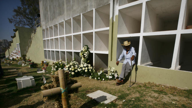 A relative leans on a burial chamber during the graveside ceremony for Eva Melchor, a victim of the Mexico oil company office building explosion, in Mexico City, Saturday, Feb. 2, 2013. Melchor died Thursday, in a blast that collapsed the lower floors of Petroleos Mexicanos, or Pemex, headquarters, crushing at least 33 people beneath tons of rubble and injuring 121. (AP Photo/Marco Ugarte)