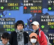 Pedestrians pass a share prices board in Tokyo. Asian markets fell Wednesday, following losses on Wall Street, as traders fret US lawmakers will not agree a deal to avert the fiscal cliff