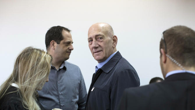Former Israeli Prime Minister Ehud Olmert, center, waits in a courtroom before a hearing in Jerusalem's District Court on Monday, March 30, 2015. The court later found Olmert guilty of accepting bribes in a retrial of corruption charges. (AP Photo/Abir Sultan, Pool)