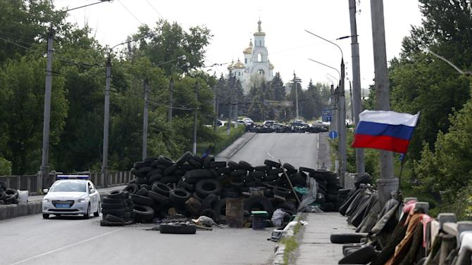 """A car passes by the barricades with a Russian national flag on a road leading into Slovyansk, eastern Ukraine, Tuesday, May 13, 2014. Pro-Russian insurgents, who have seized government buildings and clashed with government forces during the past month, held Sunday's referendum, which Ukraine's acting president called a """"sham"""" and Western governments said violated international law. (AP Photo/Darko Vojinovic)"""