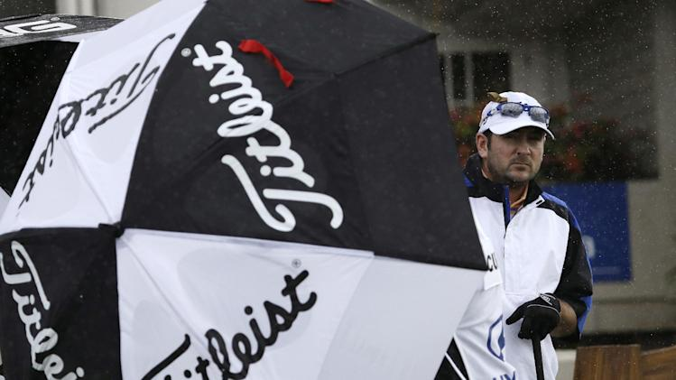 Ben Curtis peers from behind an umbrella protecting him from a driving side-wind as he prepares to tee off on the first hole at the Tournament of Champions golf tournament Friday, Jan. 4, 2013, in Kapalua, Hawaii. The tournament day was scratched later because of wind and rain. (AP Photo/Elaine Thompson)