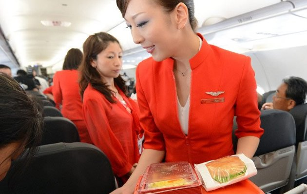 <p>Up in the air: Air Asia Japan's cabin attendants provide the in-flight meal. (AFP photo)</p>