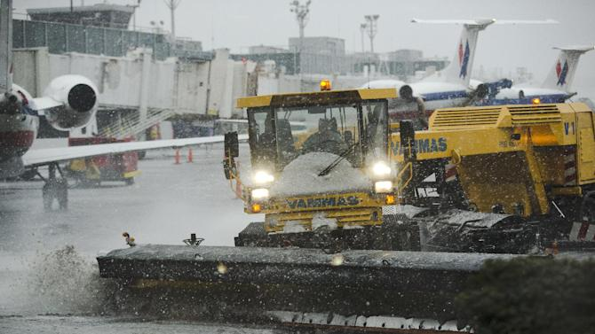 Grounds crews clear the tarmac at LaGuardia Airport in New York Friday, Feb. 8, 2013. Airlines scratched more than 3,700 flights in the Northeast through Saturday as snow began falling in what was predicted to be a huge blizzard that could dump 1 to 3 feet of snow from New York City to Boston and beyond. (AP Photo/Frank Franklin II)
