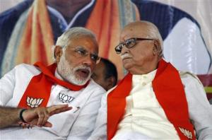 BJP leader Advani listens to BJP prime ministerial candidate Modi during a workers' party meeting at Gandhinagar