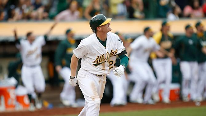 Oakland Athletics' Josh Donaldson watches his two-run home run against the Philadelphia Phillies in the 10th inning of a baseball game Sunday, Sept. 21, 2014, in Oakland, Calif. Oakland won 8-6. (AP Photo/Tony Avelar)