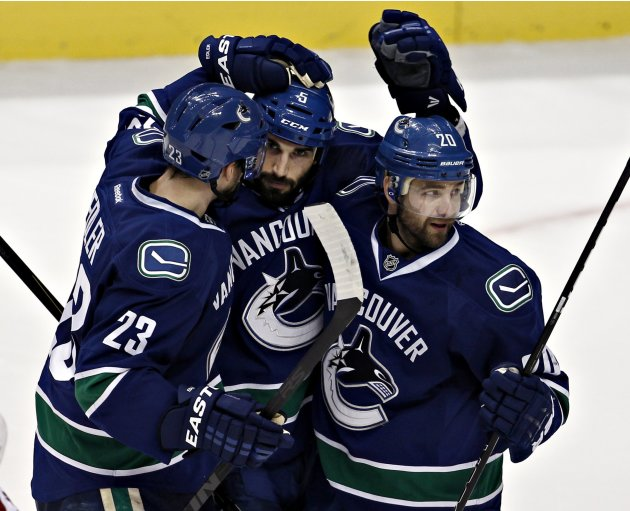 Canucks' Garrison congratulated by teammates Edler and Higgins after scoring against the Coyotes during NHL hockey in Vancouver