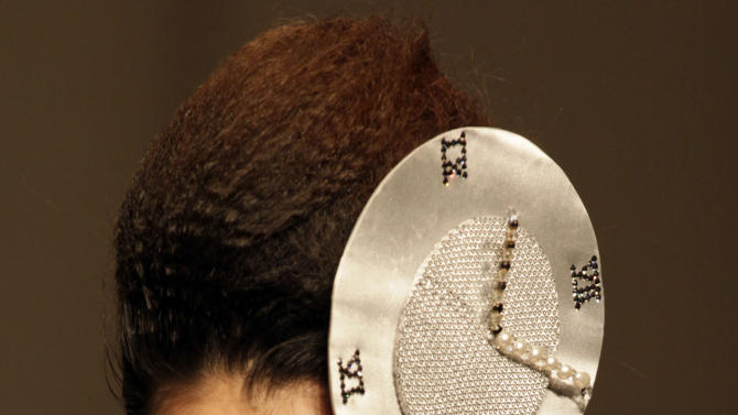 A model wears a clock head dress during a fashion show for the Dorain Ho collection at China Fashion Week in Beijing, China on Thursday, Oct. 28, 2010. (AP Photo/Ng Han Guan)
