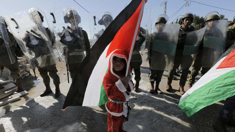 A Palestinian boy dressed as Santa Claus stands in front of Israeli soldiers during a protest near Bethlehem