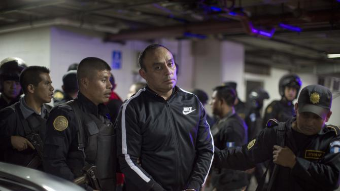 Former Guatemalan Army Captain Byron Lima Oliva, center, sentenced in 2006 to 20 years in prison for the 1998 slaying of Bishop Juan Jose Gerardi, is escorted by police agents as he arrives to a courtroom in Guatemala City, Wednesday, Sept. 3, 2014. Prosecutors said that Lima built an illicit business empire in prison by extorting money from other inmates in return for favors like allowing prohibited cellphones, and has been charged with money laundering and organized crime. (AP Photo/Luis Soto)