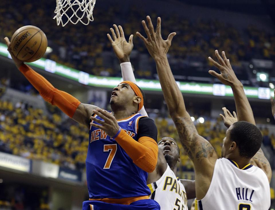 New York Knicks' Carmelo Anthony (7) shoots against Indiana Pacers' Roy Hibbert (55) and George Hill, right, during the first half of Game 6 of an Eastern Conference semifinal NBA basketball playoff series  Saturday, May 18, 2013, in Indianapolis. (AP Photo/Darron Cummings)