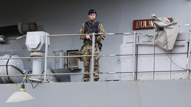 A Royal Marine patrols the deck of the Royal Navy's HMS Bulwark amphibious assault ship docked in a harbour near the Mediterranean Conference Centre which will host the Commonwealth Heads of Government Meeting in Valletta