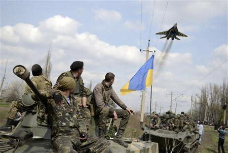 Ukrainian servicemen look at a Ukrainian military jet fly above them in Kramatorsk