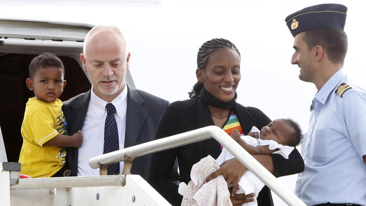 Meriam Ibrahim, from Sudan, disembarks with her children Maya, in her arms, and Martin, accompanied by Italian deputy Foreign Minister Lapo Pistelli, after landing from Khartoum, at Ciampino's military airport, on the outskirts of Rome, Thursday, July 24, 2014. The Sudanese woman who was sentenced to death in Sudan for refusing to recant her Christian faith has arrived in Italy along with her family, including an infant born in prison. An Italian diplomat who accompanied the family from Sudan said Italy leveraged its historic ties within the Horn of Africa region to help win her release. (AP Photo/Riccardo De Luca)
