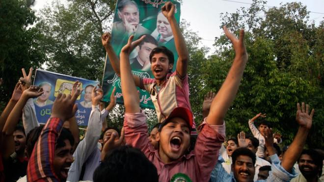 Supporters of former Prime Minister Nawaz Sharif celebrate their party's victory in Lahore, Pakistan, May 12.