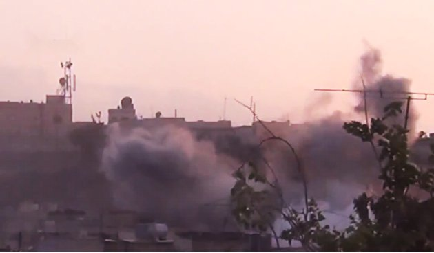 In this image made from amateur video released by the Shaam News Network and accessed Tuesday, June 26, 2012, smoke rises from buildings following purported shelling in Homs, Syria. (AP Photo/Shaam Ne