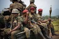 Soldiers from the Armed Forces of the Democratic Republic of the Congo (FARDC) sit in a truck on the road between Goma and Rutshuru, in the restive North Kivu province on July 11. Mutinous soldiers in DR Congo&#39;s eastern Kivu region who had handed their occupied towns back to police and UN peacekeepers gave the army an ultimatum to withdraw from the settlements