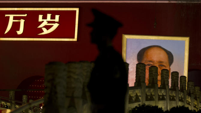 "In this photo taken Sept. 28, 2012, a paramilitary policeman guards his position while a portrait of the late communist leader Mao Zedong is moved to replace an old portrait on Tiananmen Gate in Beijing, China. The Chinese characters on the Tiananmen Gate read ""Long Live."" Despite China's dramatic transformation into an economic superpower, the authoritarian legacy of communist founder Mao Zedong continues to weigh heavily on the country's politics, leaving the vast majority of the population with little voice or knowledge of how their leaders are chosen. (AP Photo/Alexander F. Yuan)"