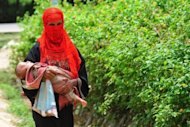 <p>A Rohingya Muslim woman walks with her child at an unregistered Burmese refugee camp in Teknaf, Bangladesh on June 20, 2012. Myanmar's government considers the Rohingya to be foreigners, while many citizens see them as illegal immigrants from neighbouring Bangladesh and view them with hostility.</p>
