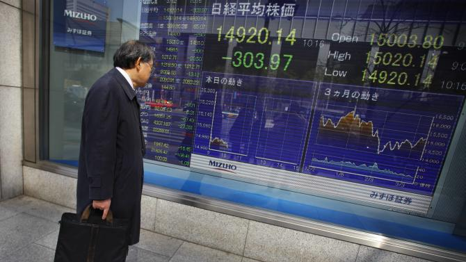 A man stops and looks at Japan's Nikkei stock update on an electric board at a securities firm in Tokyo, Wednesday, March 12, 2014. Asian stock markets sank Wednesday as recent falls in Chinese copper and iron prices added to jitters that the world's No. 2 economy is continuing to slow. (AP Photo/Junji Kurokawa)