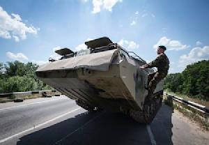 A pro-Russian separatist climbs on amphibious vehicle near a road check point outside the eastern Ukrainian city of Luhansk