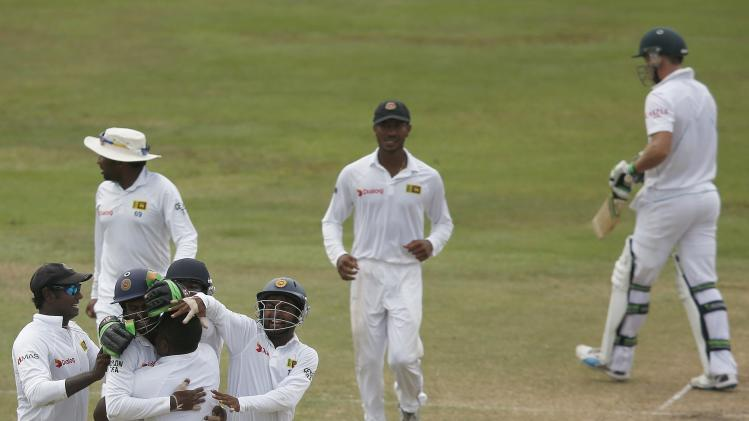 Sri Lanka's Herath celebrates with captain Mathews and teammates after taking the wicket of South Africa's de Villiers during their second test cricket match in Colombo