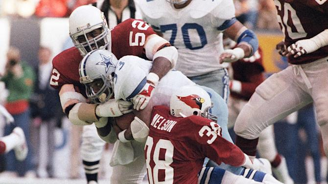 FILE - In this Nov. 14, 1983, file photo, Dallas Cowboys running back Tony Dorsett (33) is stopped after a two-yard gain by St. Louis Cardinals safety Lee Nelson (38) and linebacker Charlie Baker (52) during the second quarter of an NFL football game in Irving, Texas. Dorsett is one of at least 300 former players suing the National Football League, claiming the NFL pressured them to play with concussions and other injuries and then failed to help them pay for health care in retirement to deal with those injuries. (AP Photo/Ron Heflin, File)