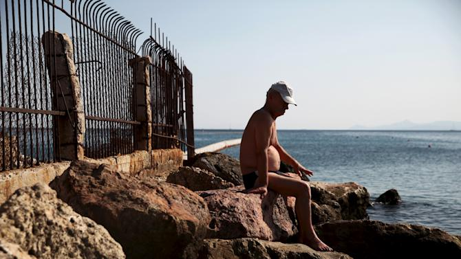 A man sits by the sea on a southern Athens suburb