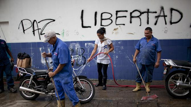 """Workers clean the street from debris left over from yesterday's clashes between anti government protestors and police in Caracas, Venezuela, Thursday, Feb. 20, 2014. The graffiti on the wall reads in Spanish """"Peace and Liberty"""". Violence is heating up in Venezuela as an opposition leader Leopoldo Lopez, faces criminal charges for organizing a rally that set off a deadly week of turmoil in anti-government protests in Caracas and other cities where demonstrators and government forces clashed leaving several dead and scores of wounded. (AP Photo/Rodrigo Abd)"""