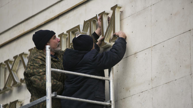 In this photo taken on Tuesday, March 18, 2014, workers remove old letters from the Crimea Parliament's building in Simferopol, Crimea. In a gilded Kremlin hall used by czars, Vladimir Putin redrew Russia's borders Tuesday by declaring the Crimean Peninsula part of the motherland - provoking a surge of emotion among Russians who lament the loss of empire and denunciations from Western leaders who called Putin a threat to the world. (AP Photo/Alexander Khitrov)
