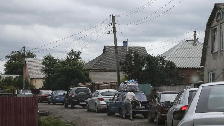Local residents fleeing from the fighting in eastern Ukraine are seen in a line of cars near Slaviansk