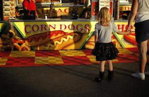 A girl looks at a food stand at the Los Angeles County Fair in Pomona