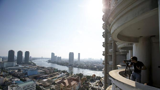 A visitor takes photograghs on a balcony of an abandoned building in Bangkok