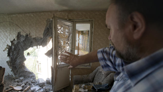In this photo taken on Wednesday, July 23, 2014, Alexander Litvinenko points to damage inflicted where a missile hit, two days before, leaving a gaping hole in the wall of his ninth-floor apartment, in Donetsk, Ukraine. The 53-year-old college philosophy teacher had just stepped into his study to check the news online, barely escaping death. Others in the residential neighborhood in northwest Donetsk were less fortunate. Five civilians were killed and 12 injured in fighting between Ukrainian government forces and pro-Russian rebels on Monday, according to the mayor's office. Residents in the rebel-held city are blaming Ukrainian President Petro Poroshenko, who has promised to stamp out the uprising in the eastern part of the country. (AP Photo/Vadim Ghirda)