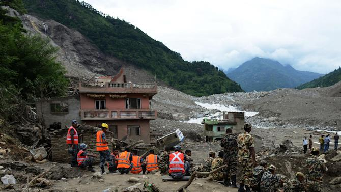 Nepalese rescue personnel gather during a recovery operation following a landslide on the Sukoshi river on August 6, 2014