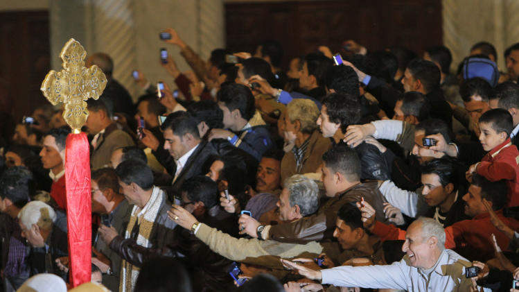 Egyptian Christians greet men carrying a cross before the arrival of Pope Tawadros II, the 118th pope of the Coptic Church of Egypt, during a midnight Mass on the eve of the Egyptian Orthodox Christmas at St. Mark's Cathedral in Cairo, Egypt, late Sunday, Jan. 6, 2013. (AP Photo/Amr Nabil)