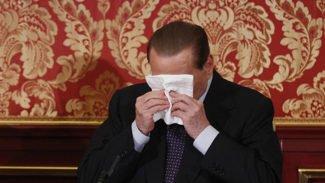 Former Italian Premier Silvio Berlusconi wipes his face during a press conference in Gerno, near Milan, Saturday, Oct. 27, 2012. Silvio Berlusconi, who announced this week he wouldn't run in spring elections, pulled an about-face Saturday and said he felt compelled to stay in politics to reform Italy's justice system after being convicted of tax fraud. (AP Photo/Luca Bruno)