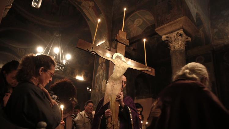 Orthodox priest carries crucifix during mass of Holy Thursday inside church at Petraki monastery in Athens