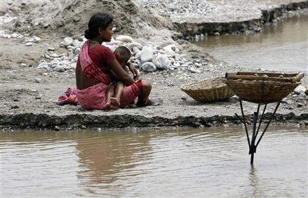 File photo of a labourer breastfeeding her child on the banks of the river Balason on the outskirts of the eastern Indian city of Siliguri