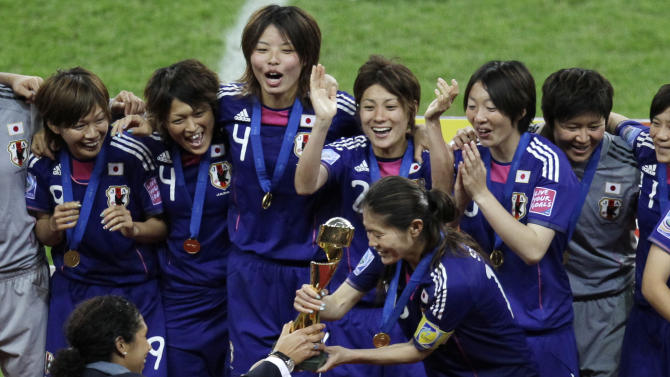 Steffi Jones, President of the Organizing Committee gives the trophy to Japan's Homare Sawa during the final match between Japan and the United States at the Women's Soccer World Cup in Frankfurt, Germany, Sunday, July 17, 2011.The Japanese women's soccer team won their first World Cup Sunday after defeating USA in a penalty shoot-out.(AP Photo/Michael Sohn)