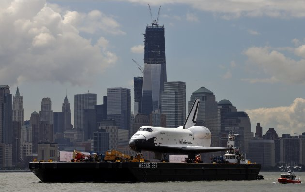 The Space Shuttle Enterprise passes lower Manhattan and the still under construction 1 World Trade Center tower as it rides on a barge in New York harbor
