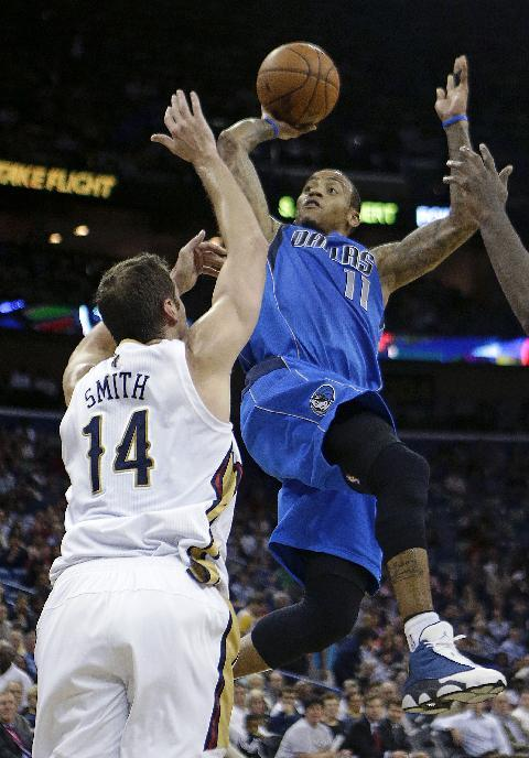 Dallas Mavericks shooting guard Monta Ellis (11) shoots over New Orleans Pelicans center Jason Smith (14) in the first half of an NBA basketball game in New Orleans, Wednesday, Dec. 4, 2013