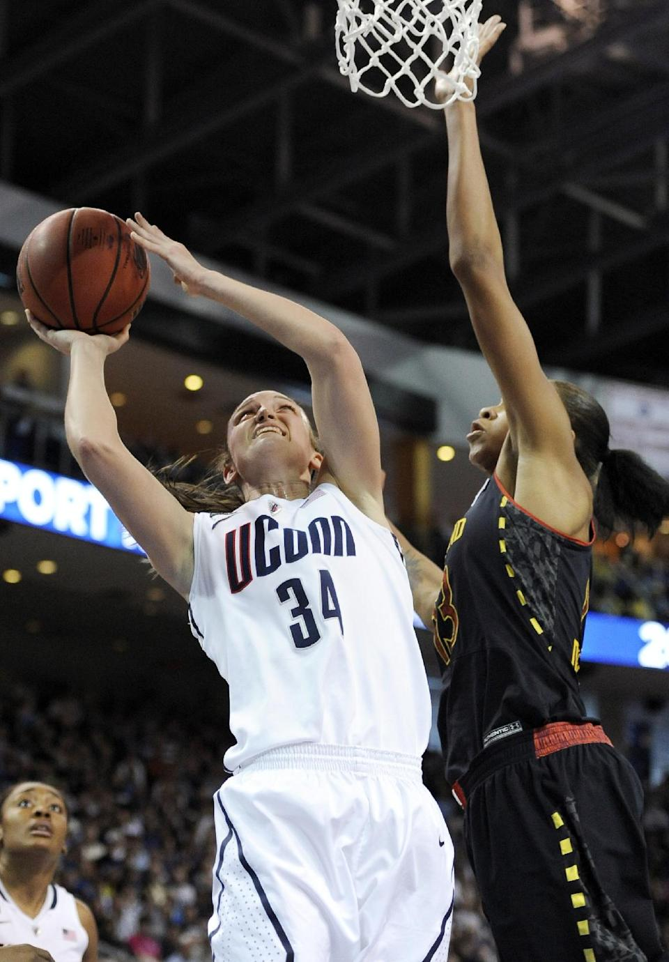 Connecticut guard Kelly Faris (34) shoots against Maryland center Alicia DeVaughn, right, during the first half of a women's NCAA college regional semifinal basketball game in Bridgeport, Conn., Saturday, March 30, 2013. (AP Photo/Jessica Hill)